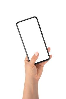 スマートフォンを保持している人間の手、孤立した白い背景の上の空白の画面に指を触れてクローズアップ、女性の手は携帯電話を保持します。女性の手はモックアップ携帯電話を保持します
