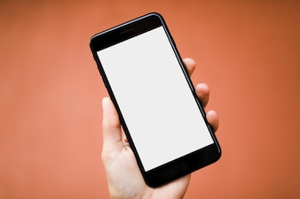 Human hand holding smartphone with blank white screen