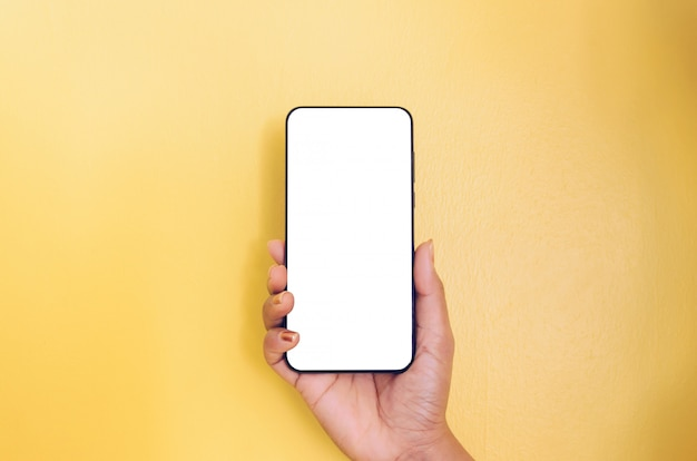 Human hand holding smartphone with white screen background.