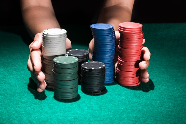 Human hand holding stack of poker chips