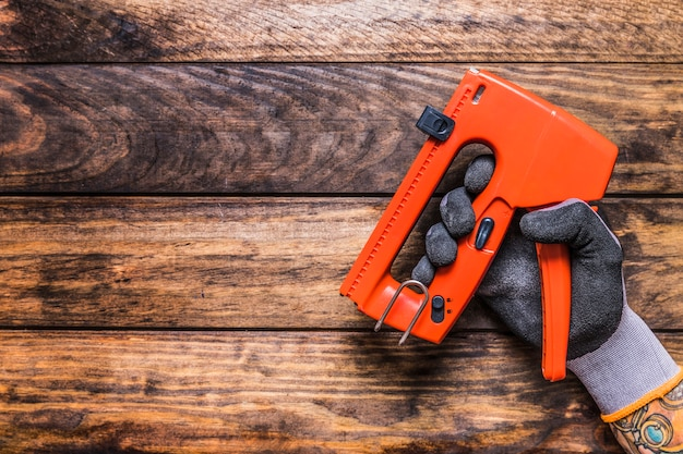 Human hand holding staple gun on wooden background