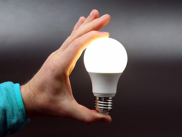 Человеческая рука, держащая включенную светодиодную лампу изолирована