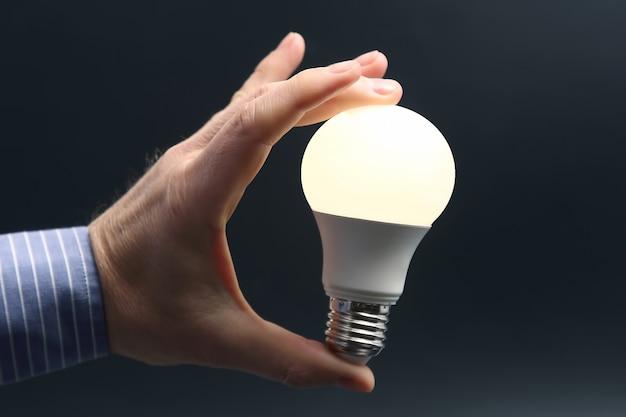 인간의 손을 어두운 배경에 포함 된 led 램프를 들고. 전기 및 led 산업