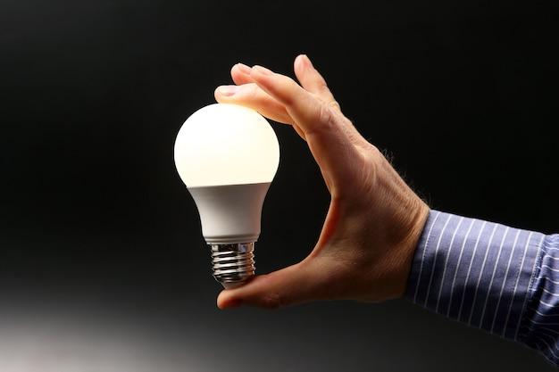 Человеческая рука, держащая включенную светодиодную лампу на темном фоне