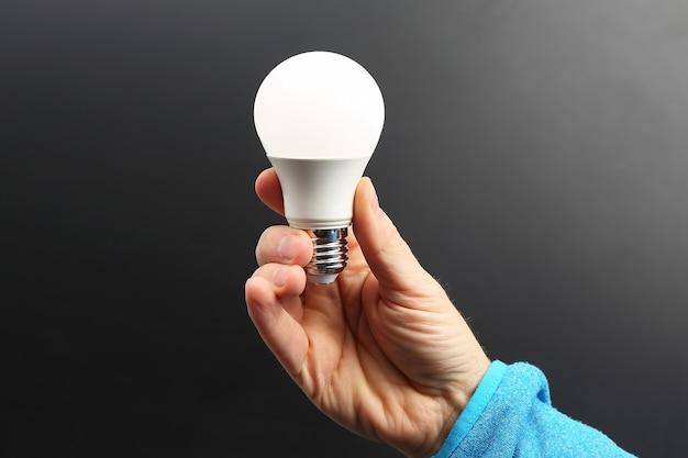 어두운 배경에 포함 된 led 램프를 들고 인간의 손