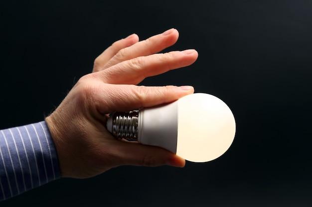 Человеческая рука, держащая включенную светодиодную лампу в темноте. электротехническая промышленность