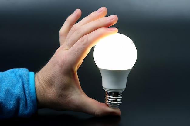 인간의 손을 어둠에 포함 된 led 램프를 들고. 전기 및 led 산업