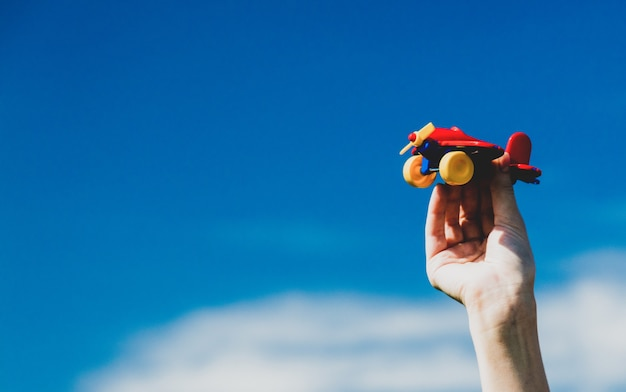 Human hand holding toy airplane