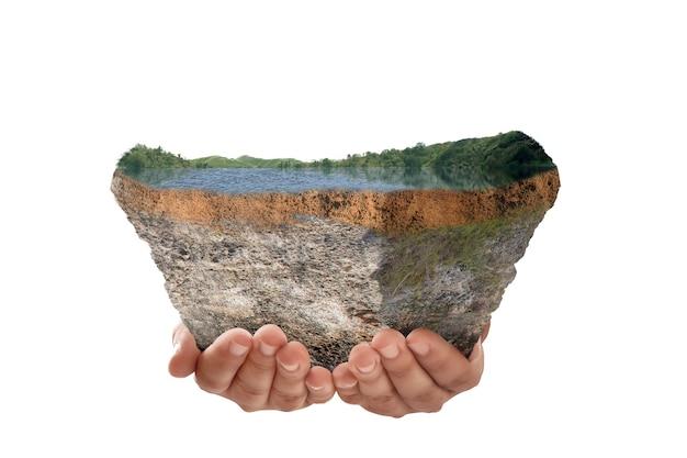 白い背景の上に分離された上部に湖と丘と断面地球の地下土壌層を保持している人間の手