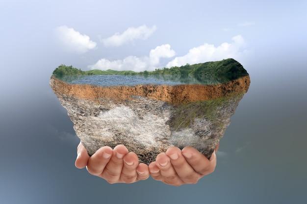 色付きの背景で上部に湖と丘と断面地球の地下土壌層を保持している人間の手