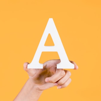 Human hand holding up the uppercase capital letter a over yellow background