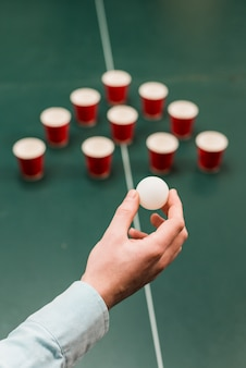 Human hand holding white ball for playing beer pong game