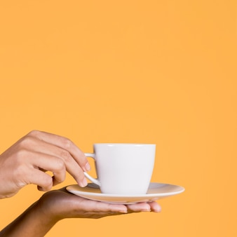 Human hand holding white ceramic coffee cup and saucer