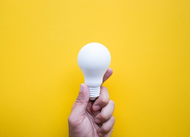 Human hand holding white lightbulb on yellow, top view
