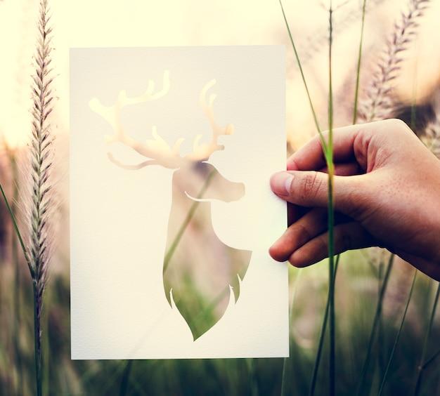 Человеческая рука с дикой жизнью лося перфорированные бумажные ремесла в nat