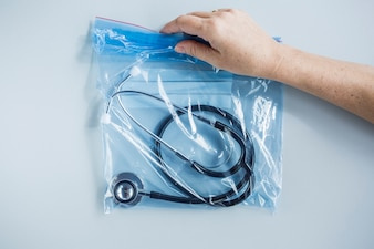 Human hand holding zip lock plastic bag with stethoscope