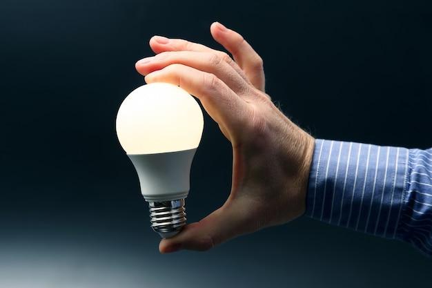Человеческая рука держит светящуюся светодиодную лампу