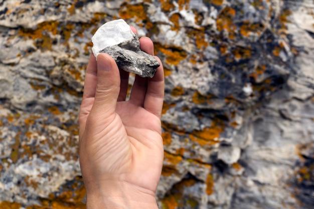 Человеческая рука держит минералогический образец известняка со слюдой на фоне скалистой поверхности