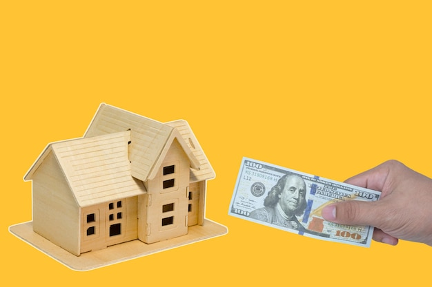 Human hand holds money with presenting and home model and with growing interest