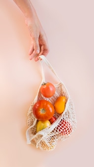 A human hand holds a string bag with tomatoes on a beige background. eco concept, healthy food, vitamins.