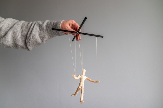 The human hand holds a wooden doll on the clothesline on a gray background with place for text. power metaphor concept
