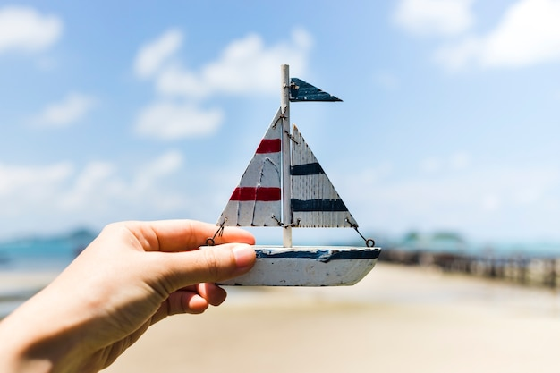 Human hand holing small sailboat