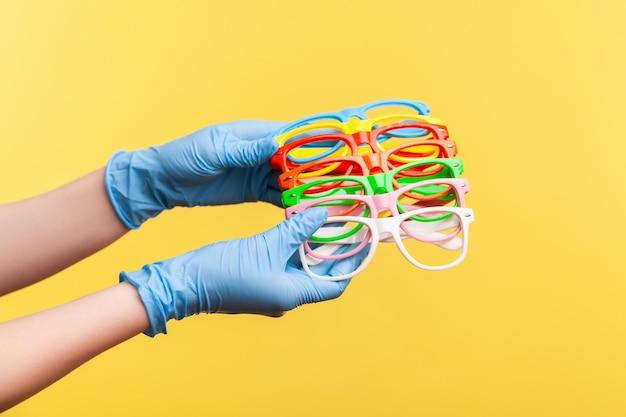 Человеческая рука в синих хирургических перчатках держит и показывает много красочных различных очков.