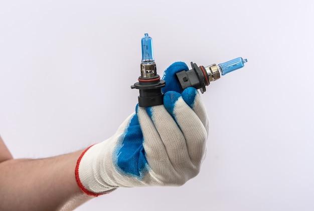 Человеческая рука в перчатке, держащая новые галогенные автомобильные лампочки, изолированные. лампа для автомобильных фар