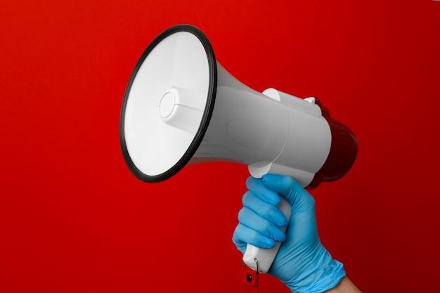 Человеческая рука в медицинской перчатке, держащая электронный мегафон на красной поверхности