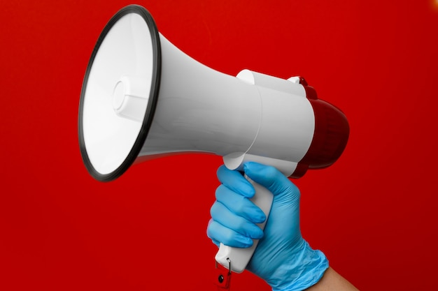 Человеческая рука в медицинской перчатке, держащая электронный мегафон на красном