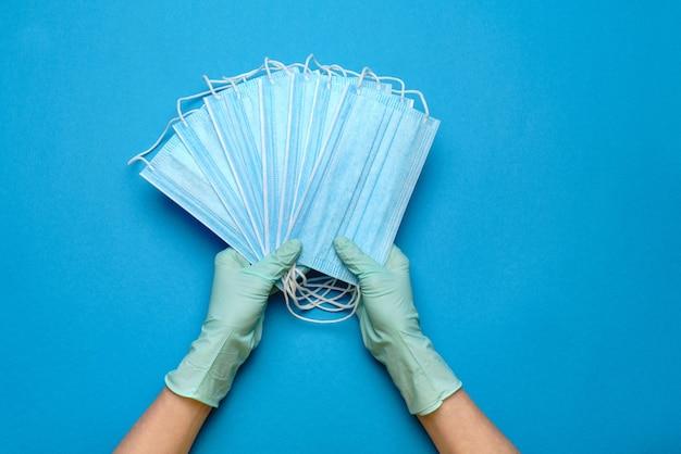 Человеческая рука в защитных перчатках, держащая защитную маску на синем фоне.