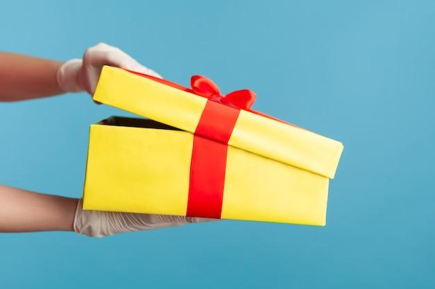 Человеческая рука в белых хирургических перчатках держит и открывает желтую подарочную коробку