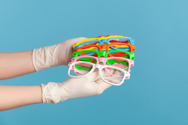 Человеческая рука в белых хирургических перчатках держит и показывает много красочных различных очков.