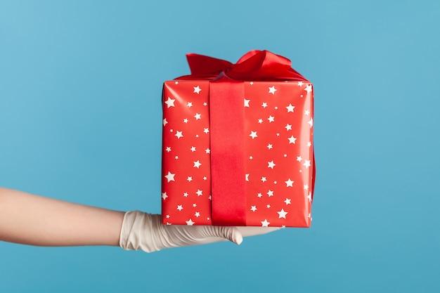 빨간 선물 상자를 들고 흰색 수술 장갑에 인간의 손. 공유, 제공 또는 배달 개념입니다.