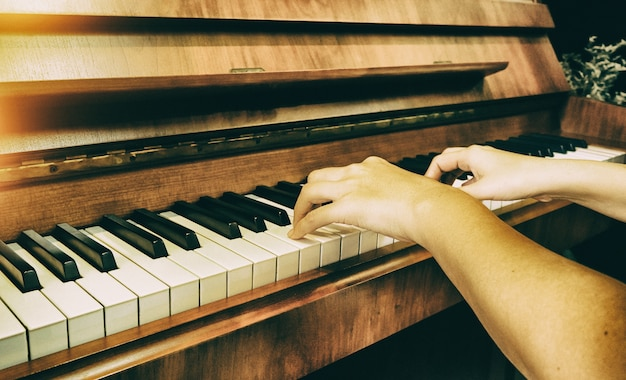 Human hand is pressing on piano key, warm light tone, blurry light around