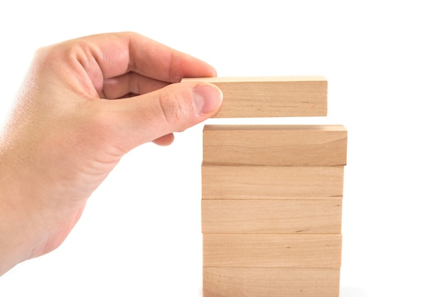 The human hand lays down wooden blocks. business development concept