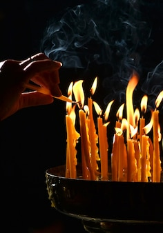 Human hand lights a candle in the church