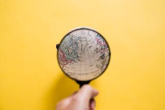 Human hand looking at globe through magnifying glass