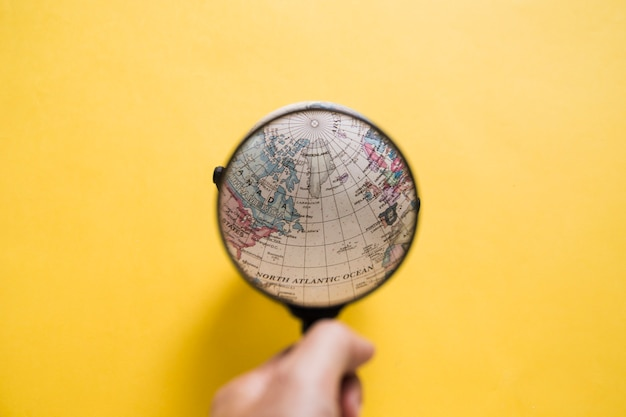 Human hand looking at globe through magnifying glass