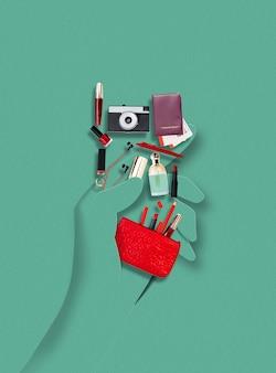 アクセサリーや所持品、週末の化粧品、緑の背景に休暇を保持する紙で作られた人間の手。現代的なカラフルで概念的な明るいアートコラージュ、コピースペース付きのモックアップ。