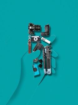 Человеческая рука из бумаги, держащая аксессуары и вещи для фото и видео ролика на синем фоне. современный красочный и концептуальный яркий художественный коллаж, макет с copyspace.