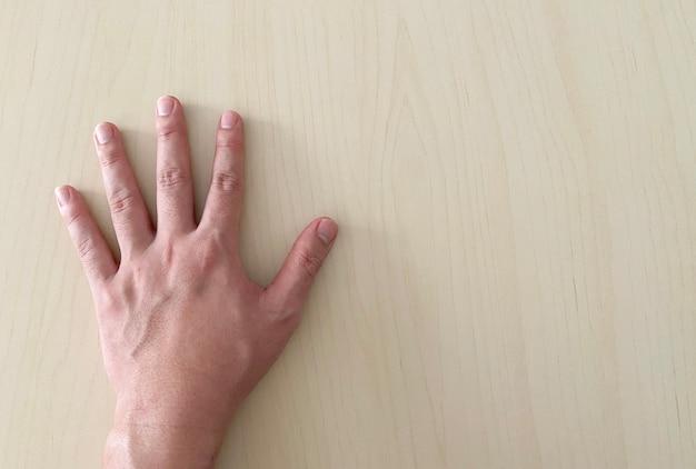 인간의 손으로 나무 책상 테이블에 안녕 5 기호를 만들기.