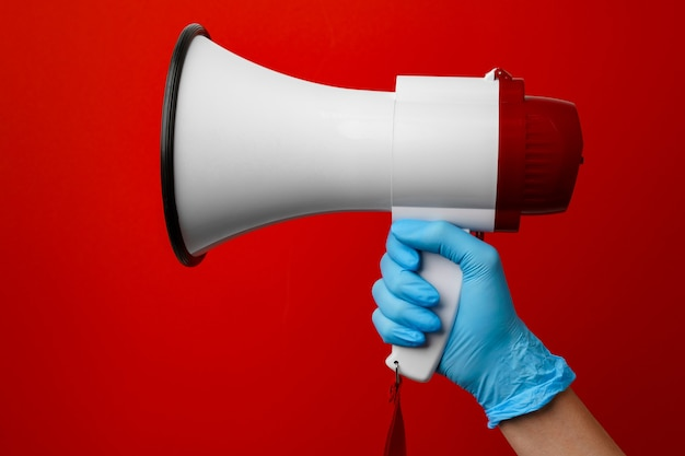 Human hand in medical glove holding electronic megaphone on red background