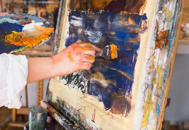 페인트 브러시와 캔버스에 인간의 손 그림