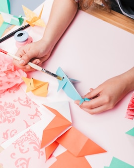 Human hand painting origami fish using paintbrush