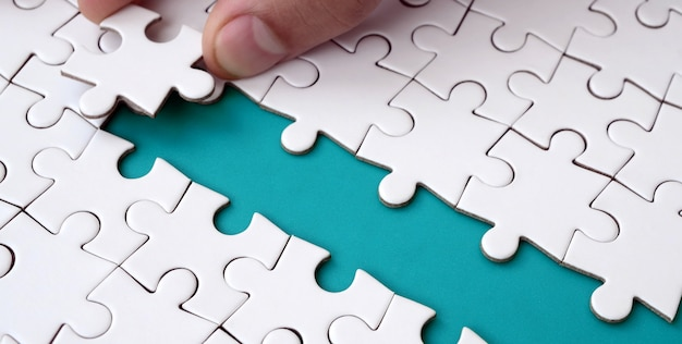 The human hand paves the way to the surface of the jigsaw puzzle, forming a blue space.