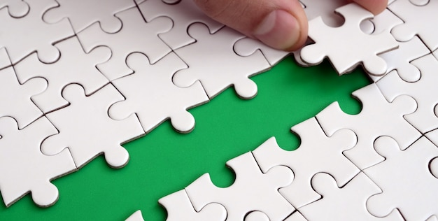 The human hand paves the way to the surface of the jigsaw puzzle, forming a green space