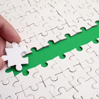 The human hand paves the way to the surface of the jigsaw puzzle
