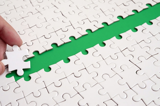The human hand paves the way to the surface of the jigsaw