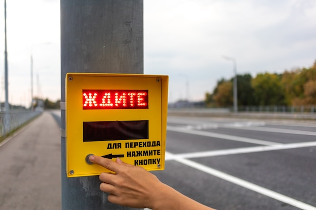 Human hand presses the button of the pedestrian crossing with the red inscription wait.